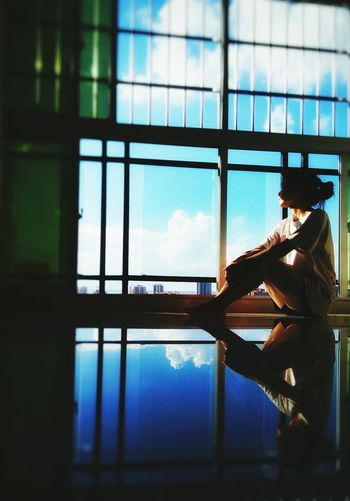 Surface level view of woman sitting by window with reflection on tiled floor at home