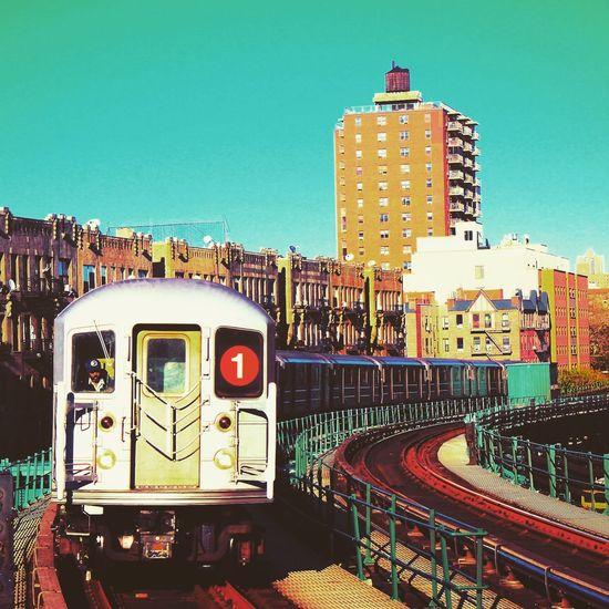 Train against illuminated buildings in city against clear sky