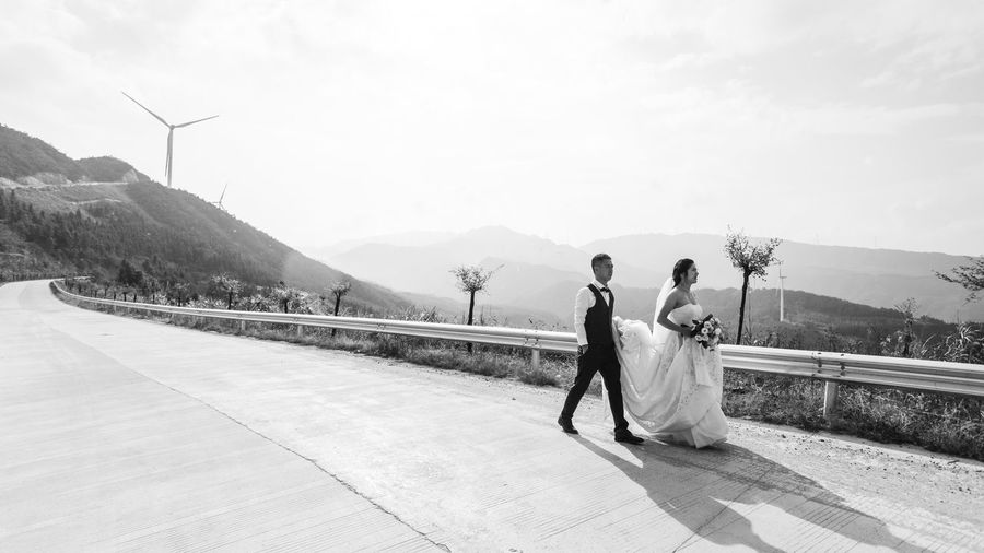 Rear view of couple walking on mountain against sky
