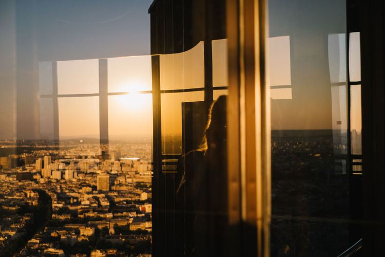 Buildings against sky during sunset seen through glass window