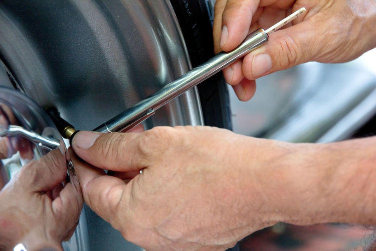 Cropped Image Of Repairman Working On Car Tire