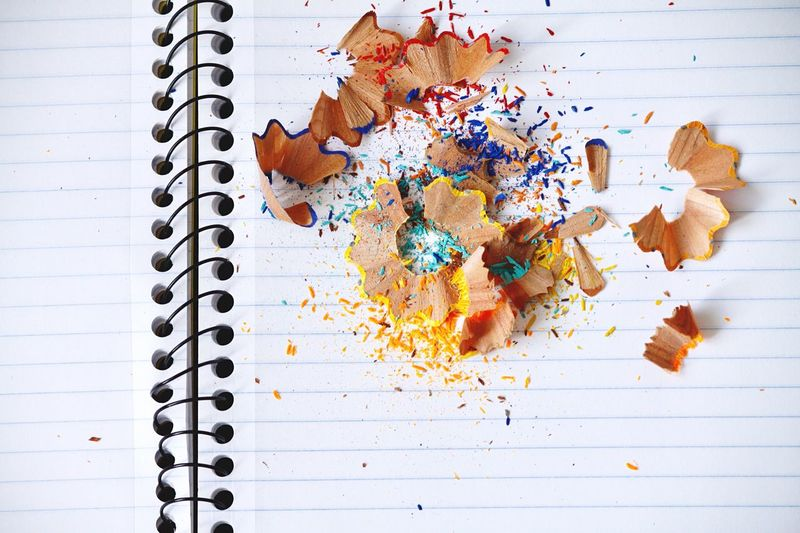 High angle view of multi colored pencil shavings on book