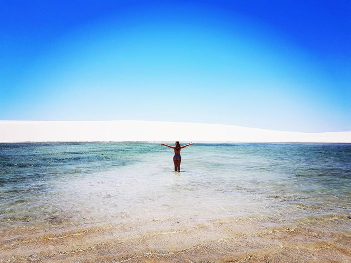 Rear view of woman with arms outstretched standing in sea against clear sky