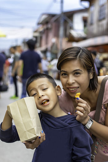 Portrait of smiling mother with son eating popcorn while standing on street in city