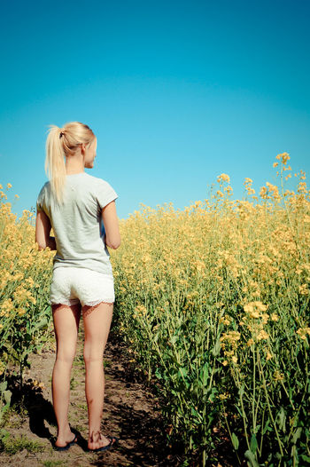 Rear view full length of young woman standing at oilseed rape