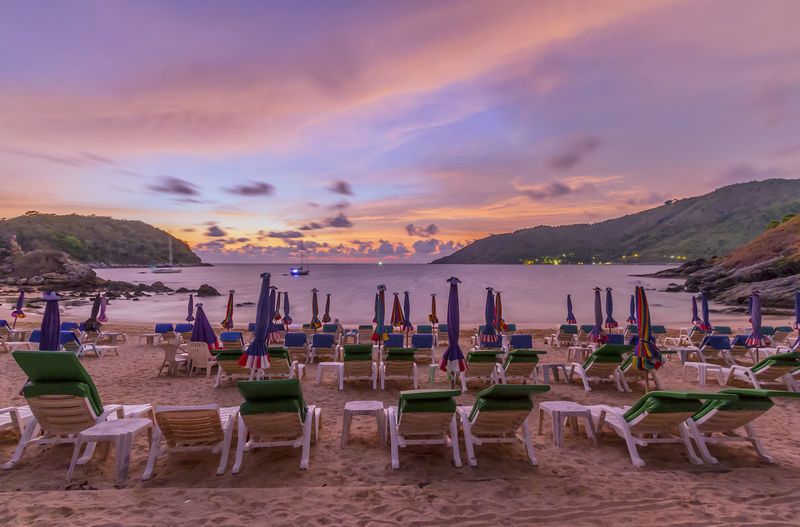 Chairs And Umbrella Arranged At Beach Against Cloudy Sky During Sunset