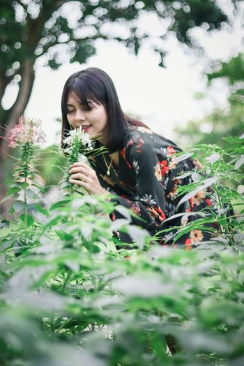 Young woman touching flowers on plants