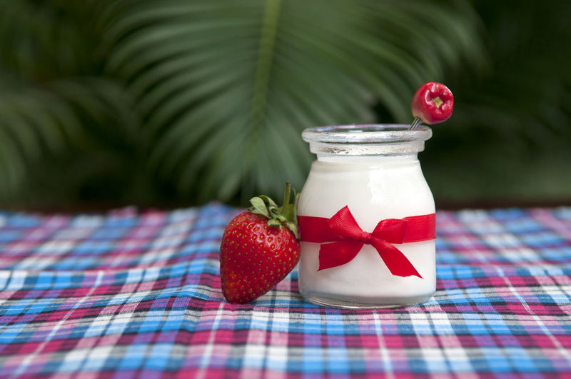 Jar with yogurt and strawberries on tablecloth