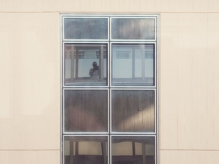 Digital composite image of man and woman standing by window of building