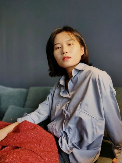 Portrait of young woman sitting on sofa at home