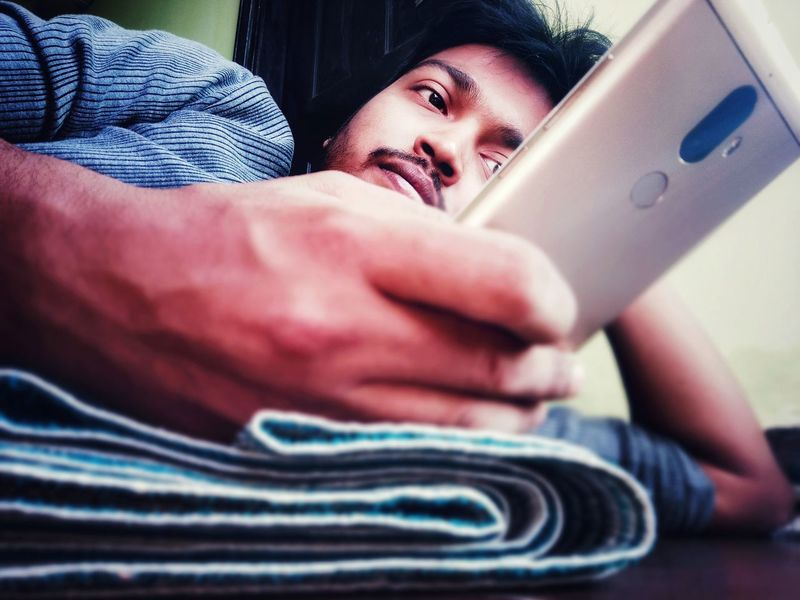 One hand business, an Indian male using mobile phone, technology, using cellphone while lying Mobile Phone Using Mobile Phone Using Cellphone Lying Down Lying Technology Technology I Can't Live Without One Hand Mobile Use Close-up Personal Perspective At Home Using Human Finger