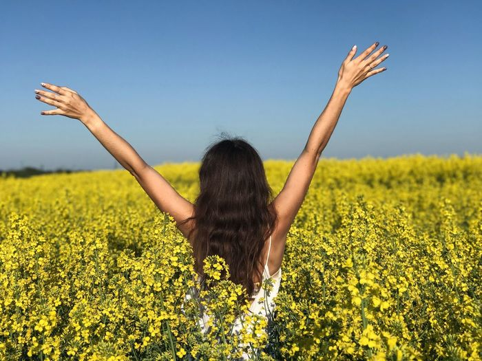 Rear view of woman with arms raised standing at rape field