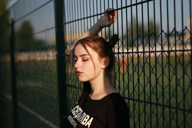 Young woman standing by fence outdoors