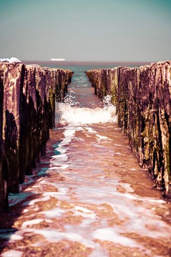 Narrow wooden posts in sea against sky