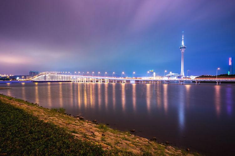 Illuminated Macau Tower And Sai Van Bridge Over Praia Grande Bay Against Sky