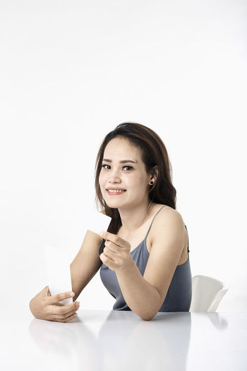 Thai Studio Shot 30-34 Years Shopping Online  Young Female Happy Asian  Laptop Beautiful Internet Attractive Smile person Computer People Portrait Holding Phone Beauty Mobile Pretty Technology Payment Adult Using Lifestyle Cheerful Purchase Business Wireless Lady Chinese Fashion Looking Smartphone Japanese  Korean Credit Card Empty Text Copy Space White Background One Person Looking At Camera Indoors  Front View Smiling Women Casual Clothing Cut Out Young Women Young Adult Sitting Hair Waist Up Hairstyle