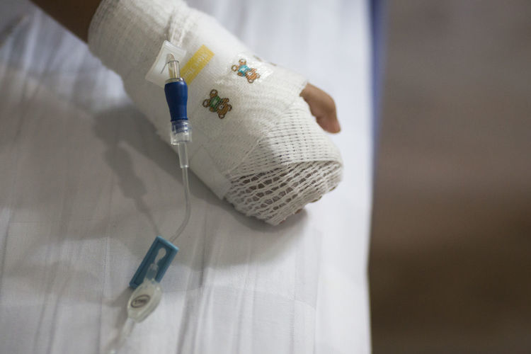 Cropped image of child with hand wrapped in bandage on bed at hospital