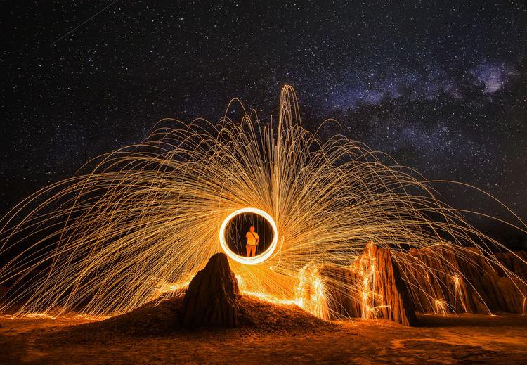 Illuminated light painting on land against sky at night