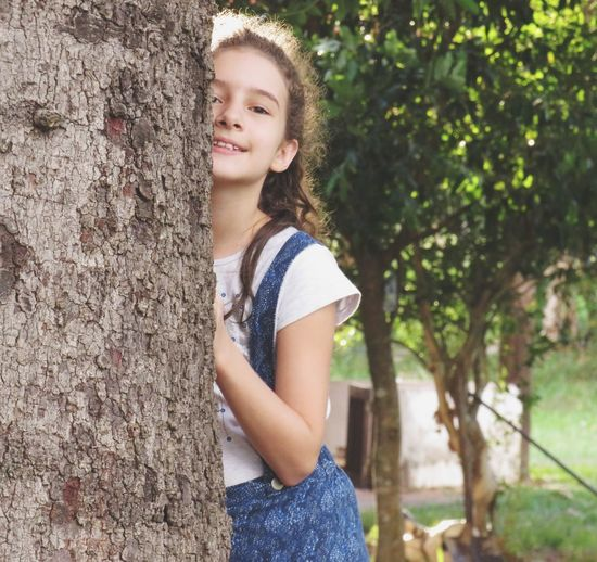 Portrait of smiling girl holding tree trunk