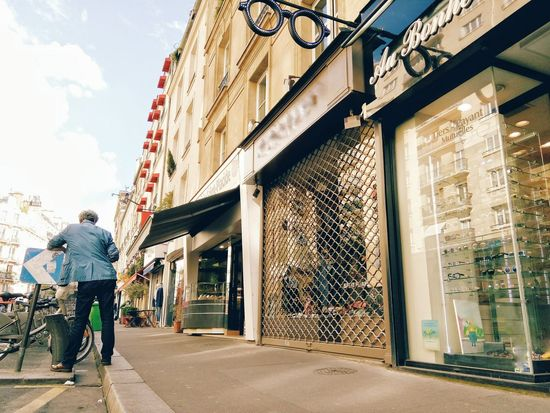 Texting break on a shopping spree in saint Germain des Prés . Attitude Binoculars Dandy Clouds And Sky Original Experiences Walking Around The City  Man Street Perspective Stores Texting Paris, France  Live Love Shop Showcase June The OO Mission The 00 Mission The City Light