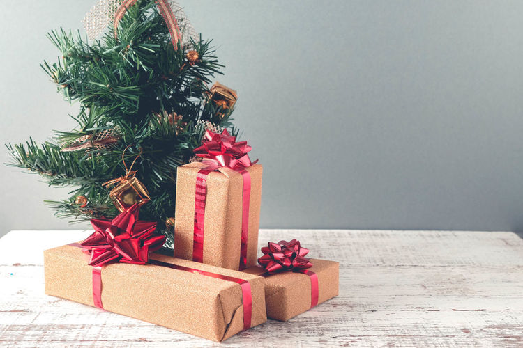 Christmas presents on wooden table against gray wall