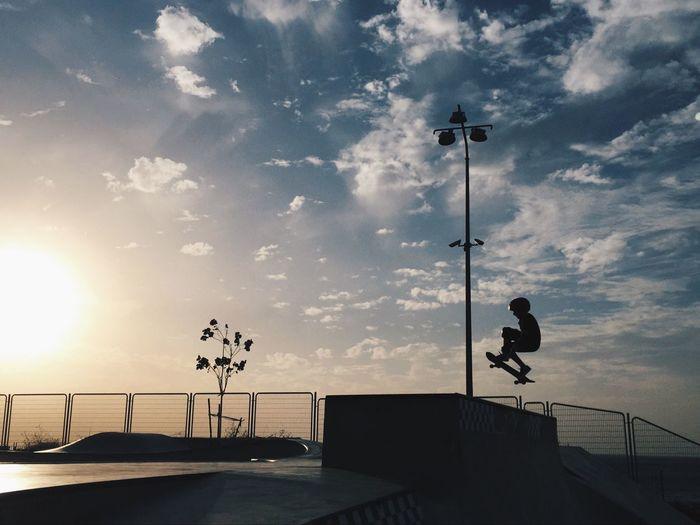 Silhouette Skateboarder Skateboarding In Park Against Sky During Sunset