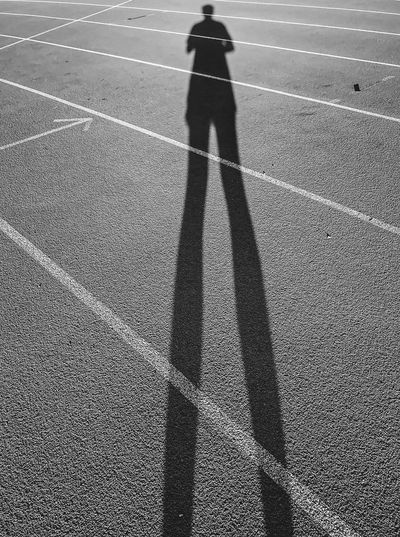 Shadow of man standing on running track