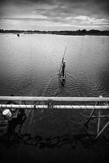 High Angle View Of Man Sailing Boat In Lake