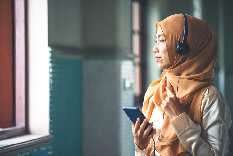Woman looking away while using smart phone