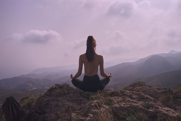 Woman meditating on mountain against sky