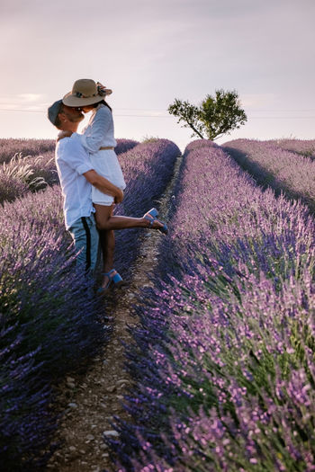 Side view of couple standing on flowering field against sky