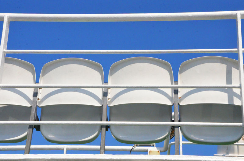 Low angle view of bleachers against clear blue sky