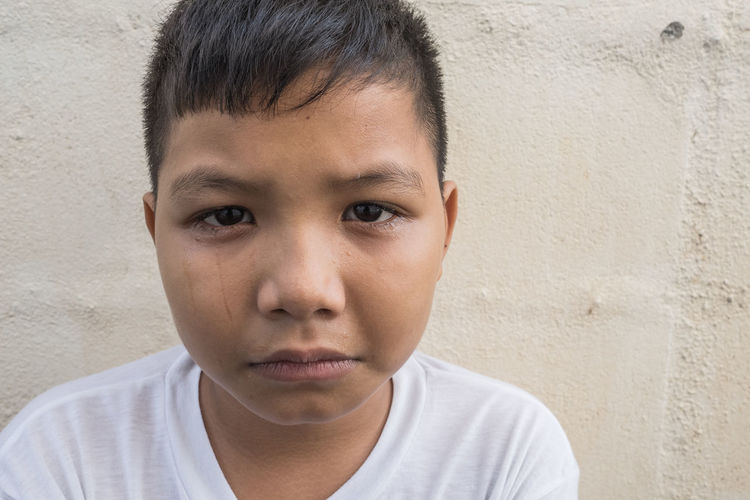 Close-up portrait of boy crying while standing against wall