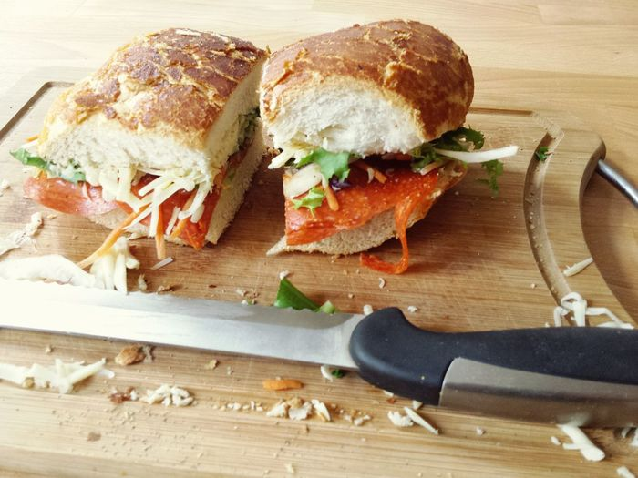 Close-Up Of Pepperoni Sandwich With Knife On Cutting Board
