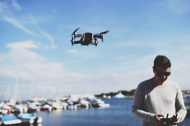 Man flying drone while standing at sea