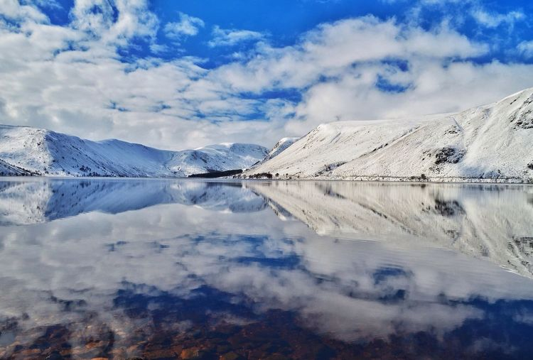 Idyllic Shot Of Snowcapped Mountains Reflection In Lake Against Sky
