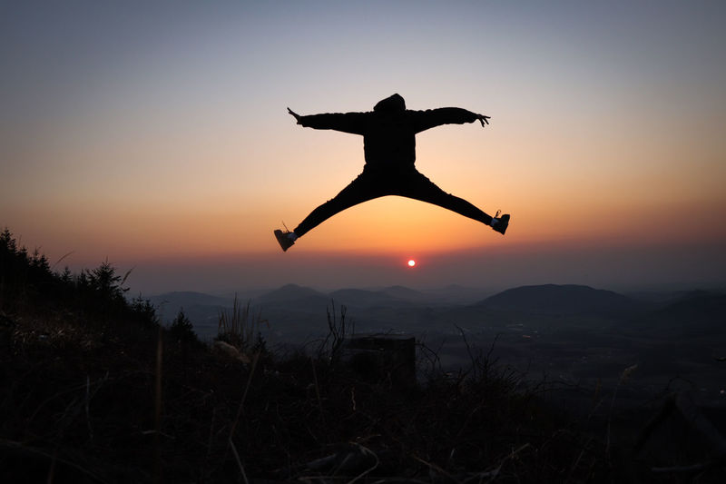Silhouette of woman flying against sky during sunset