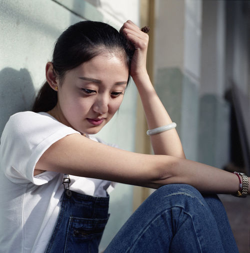 Depressed Woman Sitting Against Wall