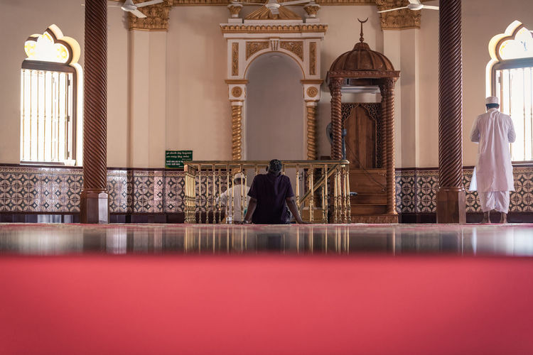 Rear view of people praying in mosque