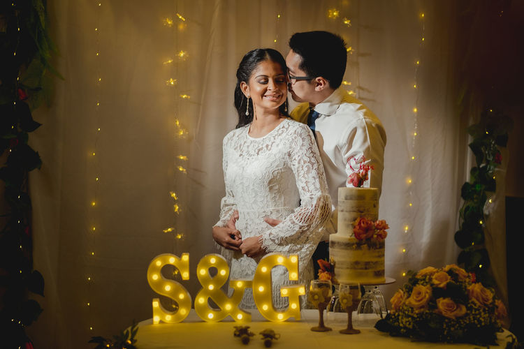 Romantic newlywed couple standing by table in wedding ceremony