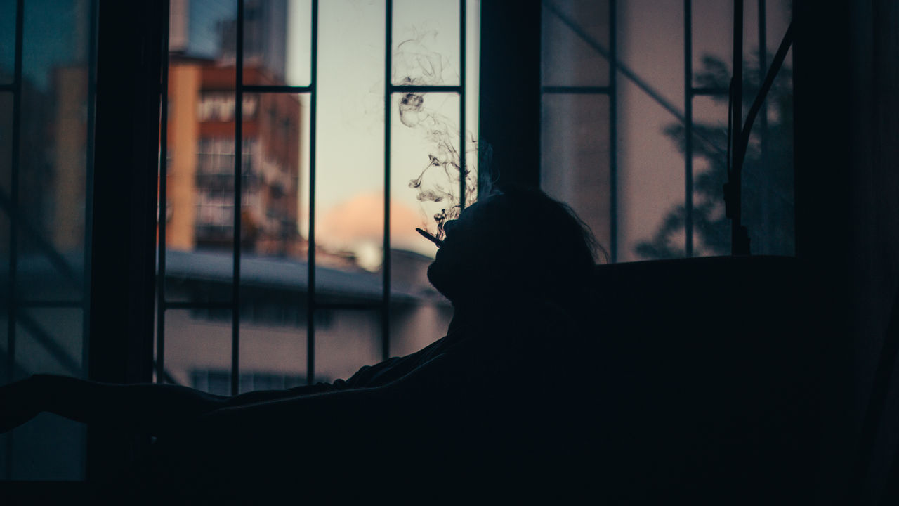 Silhouette of man smoking against window at home