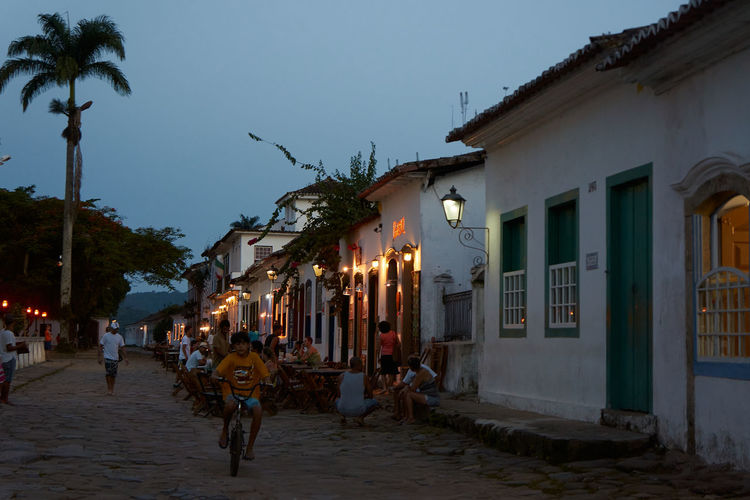 People on street amidst buildings in city at dusk
