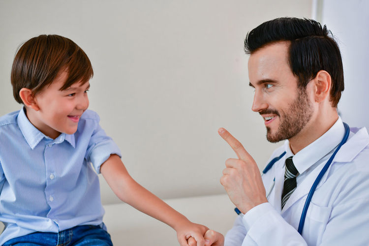 Cheerful Doctor And Boy Gesturing At Hospital