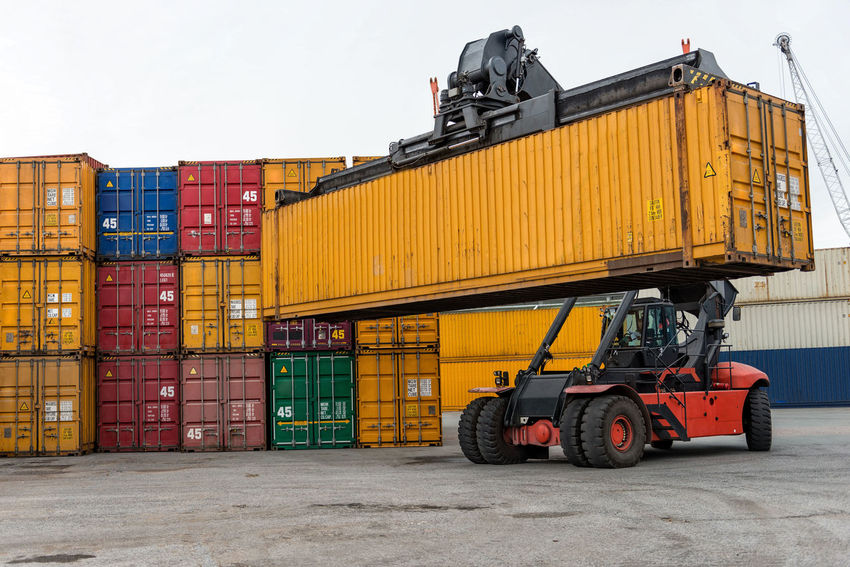 Mobile stacker handler in action at a container terminal. Harbor Cargo Container Commercial Dock Container Day Export Freight Transportation Import Industry Land Vehicle Logistic Nautical Vessel No People Outdoors Shipping  Sky Stack Terminal Transfer Transportation