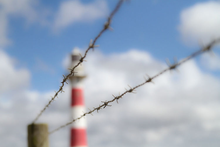 Close-up of barbed wire against lighthouse