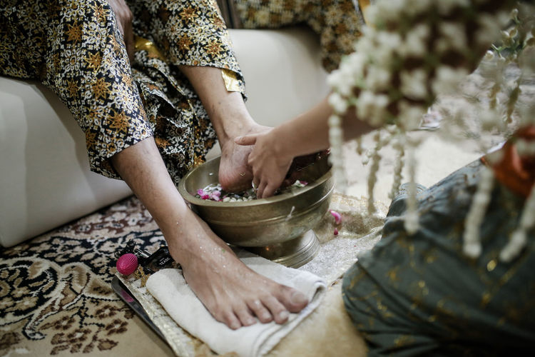 Midsection of bride washing woman legs on floor