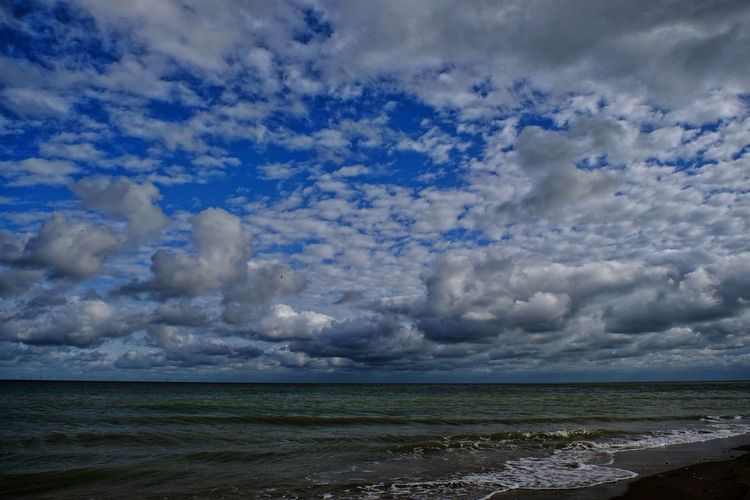 View of calm sea against cloudy sky