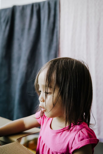 Close-up of girl with cardboard box at home