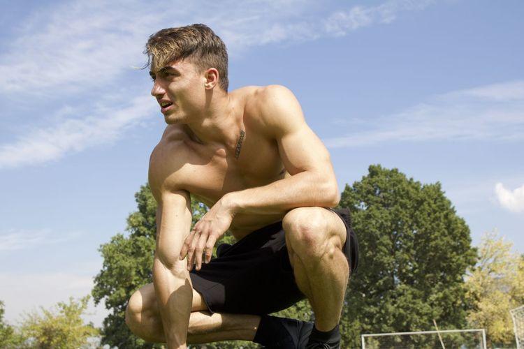 Shirtless Man Crouching Against Sky