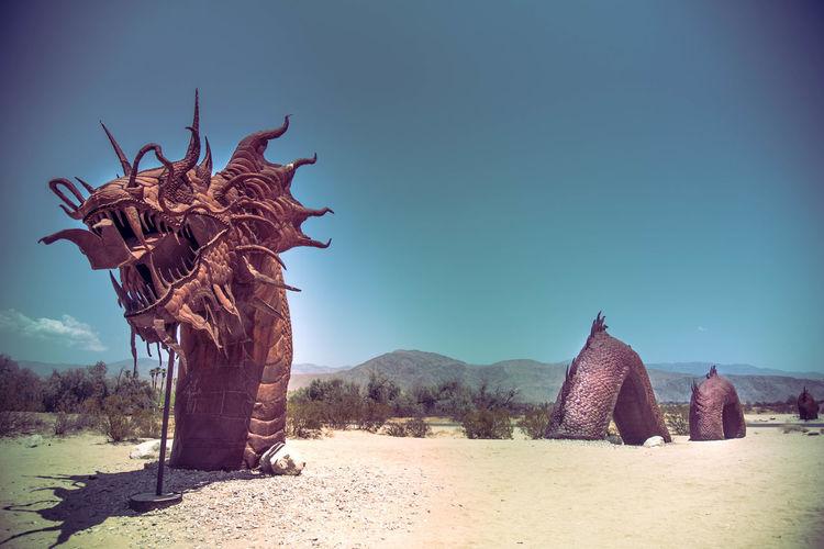 View of sculpture on landscape against blue sky